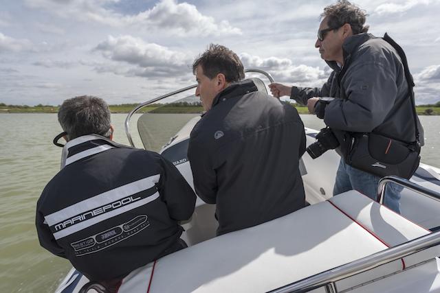 Trois hommes font un test de navigation sur petit bateau à moteur